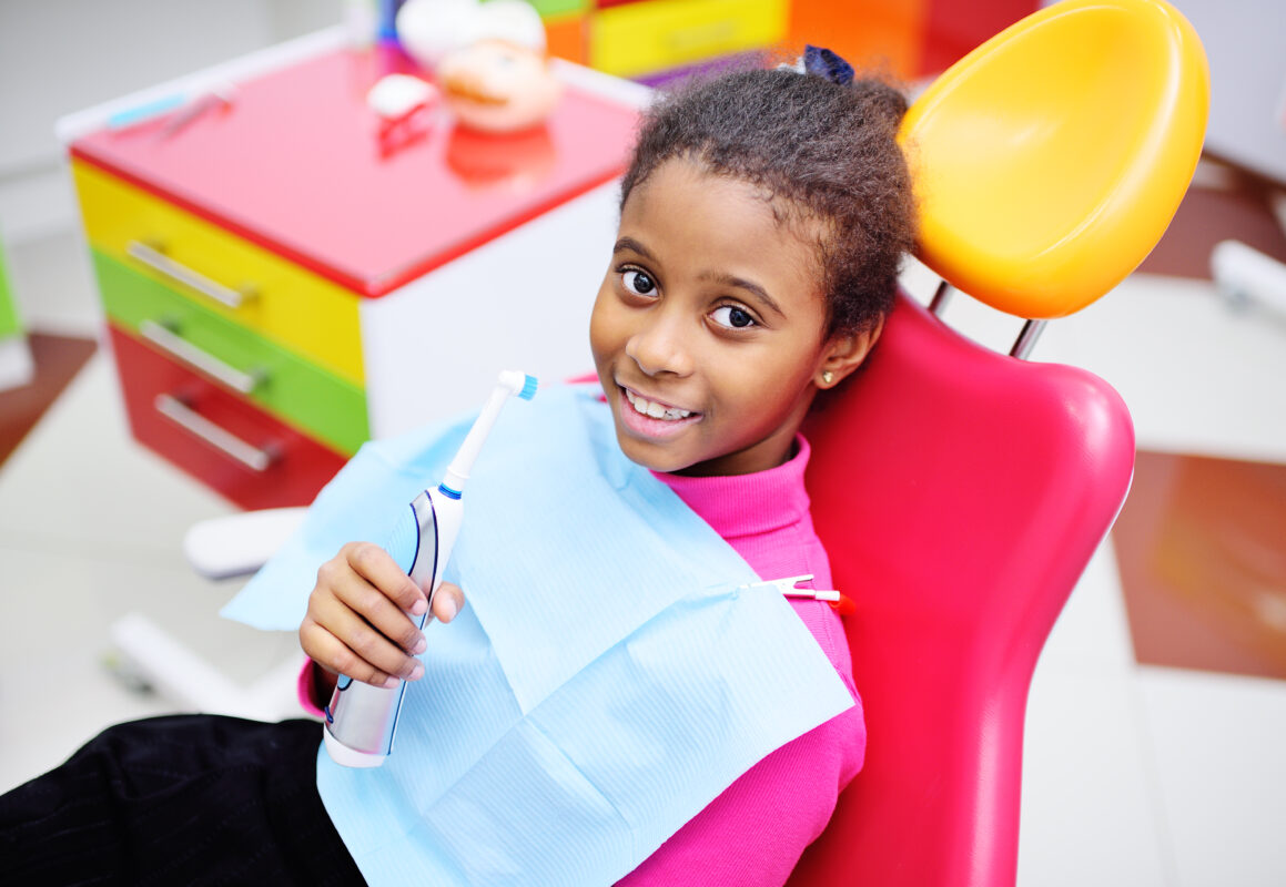 DENTAL INJURIES IN CHILDREN: Image showing a happy girl on a dental chair