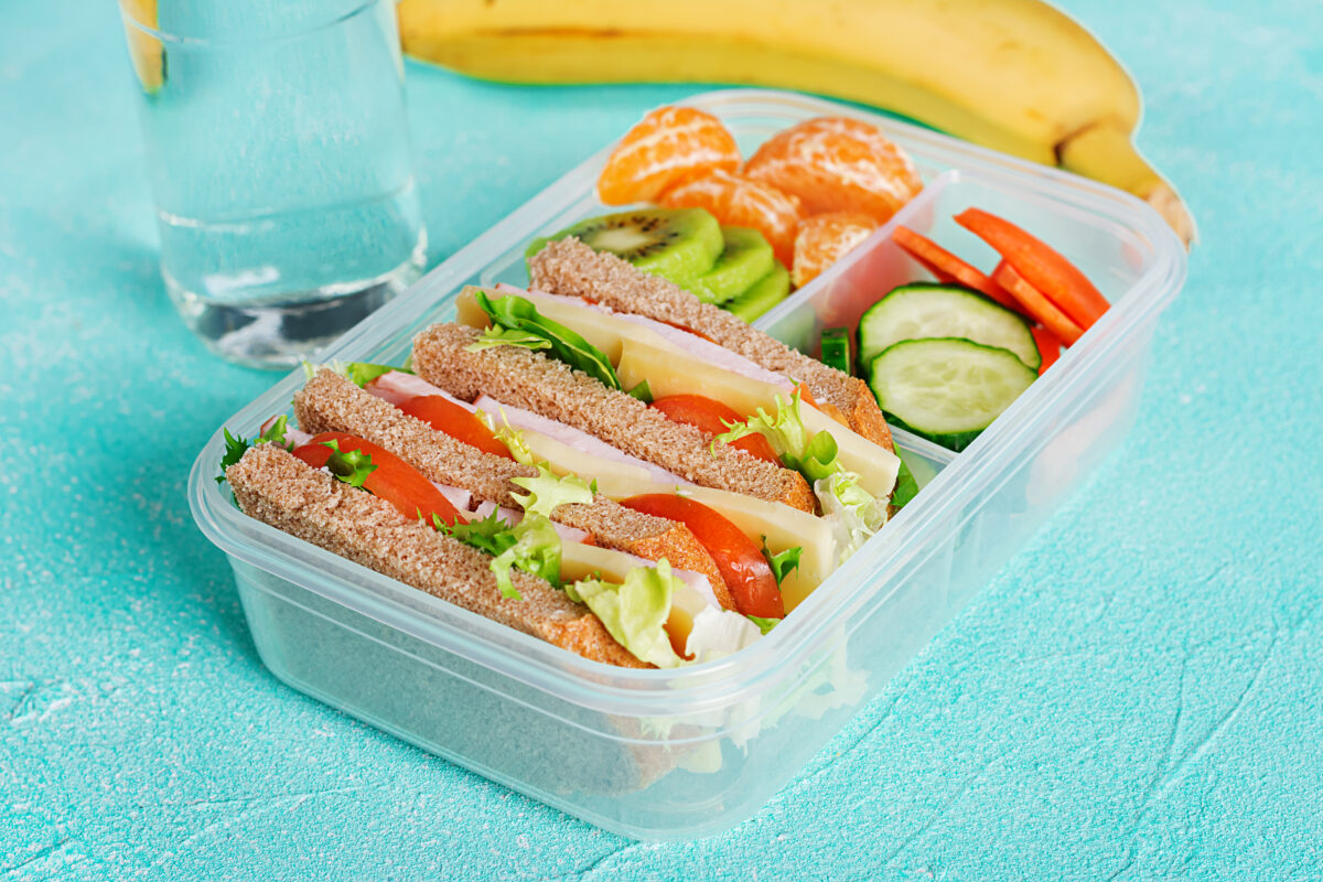Preventive dental care: School lunch box with sandwich, vegetables, water, and fruits on table. Healthy eating habits