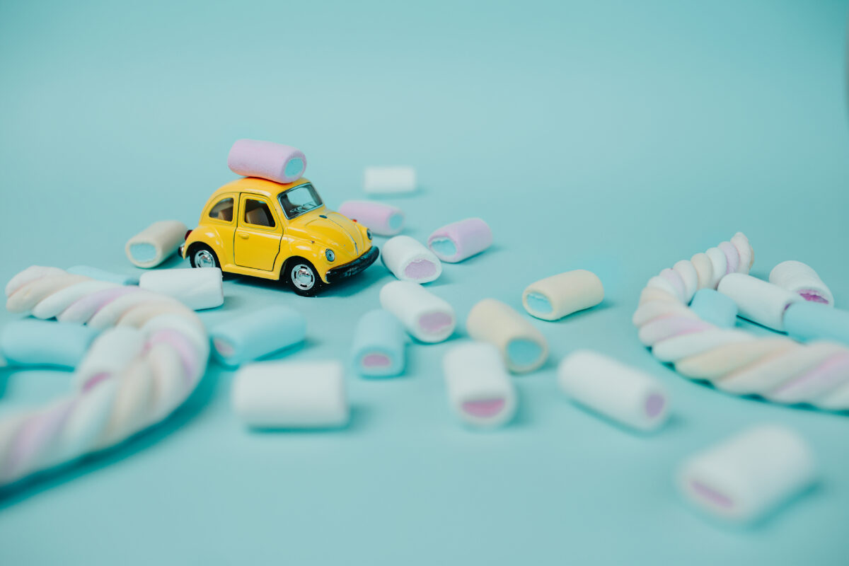 SWEET TOOTH : An illustration showing yellow toy car with twisted marshmallow and candies around.