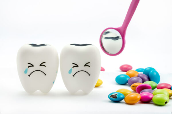 SWEET TOOTH : An illustration showing tooth decay with dental mirror and sugar coated chocolate on the side.