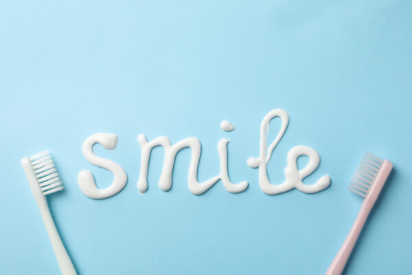 THE GOODNESS OF FLUORIDE : Word Smile made of toothpaste on blue background, top view